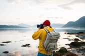 Hipster Traveler Photographer Takes A Photo Beautiful Nordic Landscape On Professional Camera. Man T poster