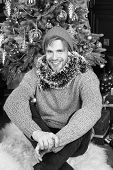 Man Smile In Hat, Sweater, Tinsel At Christmas Tree. Macho Sit On Furry Carpet At Xmas Tree In Room. poster
