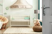 Cute Nursery Interior With Comfortable Crib Near White Wall poster
