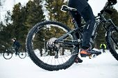 Midsection Of Mountain Biker Riding In Snow Outdoors In Winter. poster