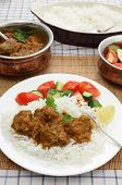 A plate of Madras butter beef curry with rice, salad and serving dishes in the background