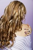 stock photo of hair streaks  - beautiful woman with long blond professionally dyed curly hair touching wearing purple manicure on purple background - JPG
