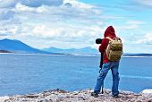Wildlife photographer traveler enjoying ocean view from top of the mountain, backpacker hiking and t