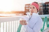 Healthy Caucasian Woman Keeping Fit In The Winter By Stretching Before Jogging In A Snow Filled City poster