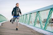 Healthy Caucasian Woman Keeping Fit In The Winter By Jogging In A Snow Filled City poster