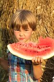 The Small Child Outdoors Eats Water-melon