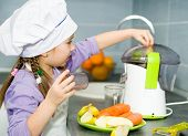 girl  making fresh apple juice with a juice extractor