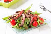 roastbeef pieces with green bean pods and tomatoes