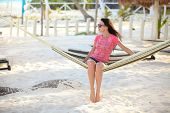 Girl sitting in hammock on the beach