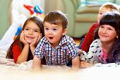 stock photo of brother sister  - group of happy kids watching tv at home - JPG