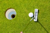 Golf player putting ball into hole, only ball, hole and iron to be seen