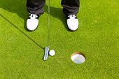 Golf player putting ball into hole, only feet and iron to be seen