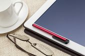 digital tablet computer with stylus pen, cup of coffee and reading glasses