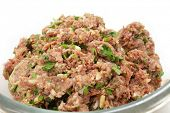 A glass bowl full of a mixture of minced beef, onion and breadcrumbs, with chopped parsley, garlic a
