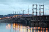 Hydroelectric power station on river at evening, posts with high-voltage wires.