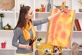 beautiful young woman painter at work, on room interior background