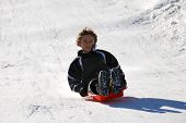 Boy Sledding Down The Hill