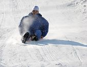 Man Sledding Down The Hill