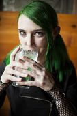 Young Woman With Beautiful Green Hair And Eyes Drinking Water