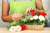 Florist makes flowers bouquet in wicker basket