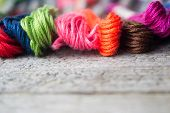 Colorful cotton craft threads on wood background with copy space