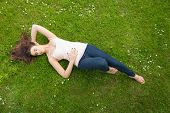 Beautiful brunette woman lying on grass on a sunny day
