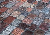 stock photo of cobblestone  - Background texture of old wet granite cobblestone road - JPG