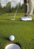 Golfer putting, selective focus on golf ball