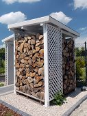 White wooden woodshed with neatly arranged chopped firewood
