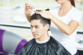 image of beauty parlour  - Female hairdresser cutting hair of smiling man client at beauty parlour - JPG