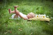 little girl on soft pillow in fresh spring grass