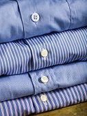 A pile of four bluish shirts on a shelf