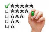 stock photo of performance evaluation  - Hand putting check mark with green marker on five star rating - JPG