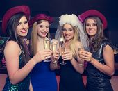 Attractive friends clinking champagne glasses at hen night looking at camera