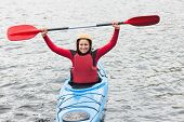 Smiling woman in a kayak cheering at the camera in the middle of a cold lake