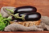 Fresh eggplants in wicker basket on table on wooden background