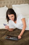 Calm pretty brown haired woman shopping online with her tablet pc in a chic bedroom