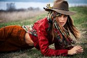 young blond woman in autumn fashion clothes, hat, red leather jacket, cashmere scarf and brown pants outdoor shot