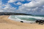stock photo of st ives  - Porthmeor beach St Ives Cornwall England by the Tate Art Gallery with white waves crashing towards the shore and known for surfing - JPG