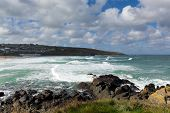 Porthmeor St Ives Cornwall England with white waves breaking towards the shore and known for s poster