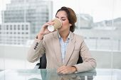 Happy businesswoman sitting at her desk drinking from disposable cup in bright office