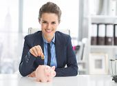 Happy Business Woman Putting Coin Into Piggy Bank