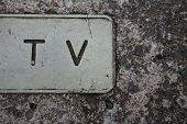 image of oblong  - TV letters carved in oblong shape within stone manhole cover - JPG