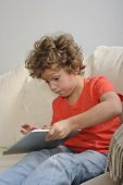 young boy playing games on a tablet