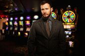 Handsome well-dressed man against slot machines in a casino