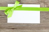 Blank Paper Sheet With Green Bow On Wooden Background
