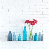 Decorative shelf on white brick wall with flowers in vase on it