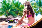 long haired yound woman in bikini lying on chaise-longue luxury pool side
