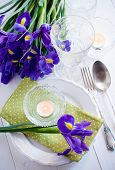 stock photo of purple iris  - Festive table setting with purple iris flowers vintage cutlery and candles.