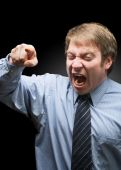 stock photo of angry man  - Upset businessman yelling on dark background focus on face - JPG